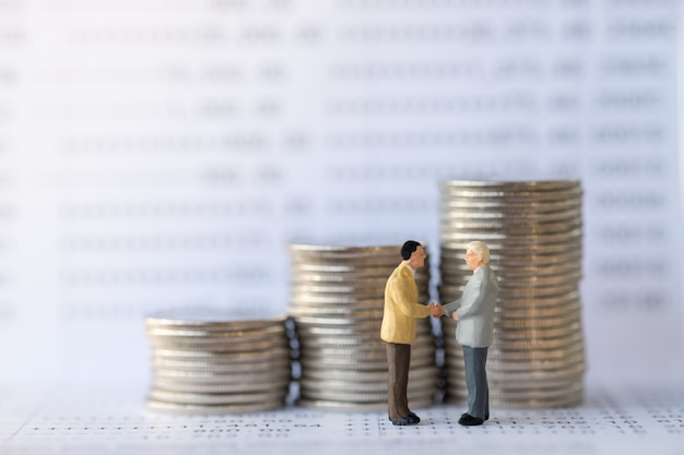 ビジネスマンのミニチュアフィギュア手がコインのスタックで銀行通帳を振る。