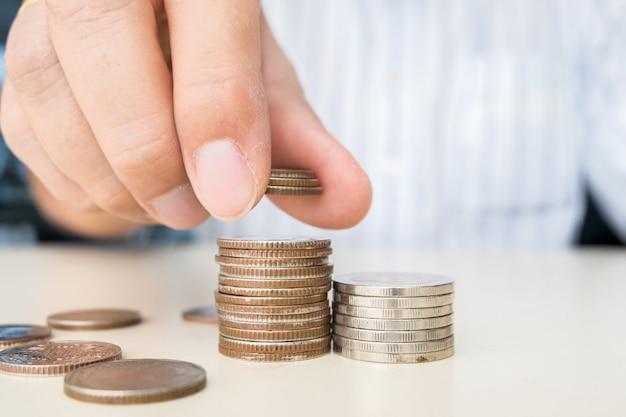 コインのスタックの一番上にコインを押しながら置く手のクローズアップ