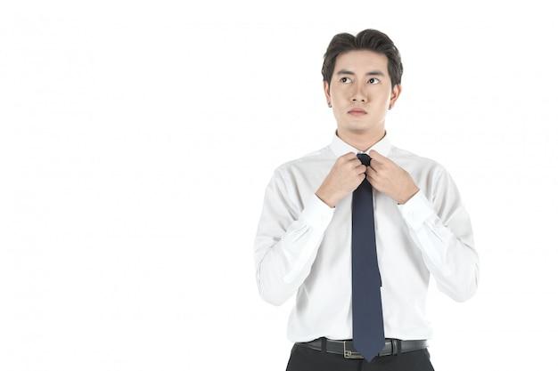 Портрет умного молодого азиатского бизнесмена регулирует и связывает галстук на изолированный