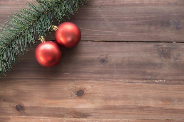 幸せな新年とクリスマスのコンセプト。テキストのコピースペースを持つ木の板にカラフルな赤い飾りボールとモックアップクリスマスツリーのフラットレイアウトビュー。