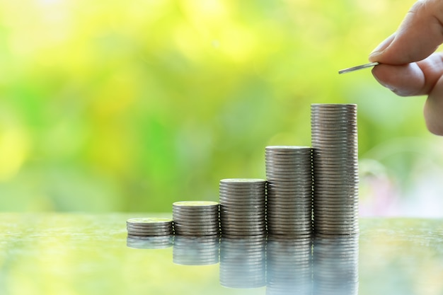 ビジネス、お金、節約、セキュリティの概念。男の手の保有物のクローズアップし、緑の葉の自然の背景とコピースペースのボケ味を持つコインのスタックの一番上にコインを置きます。