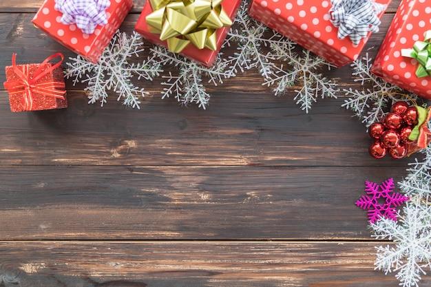 新年、クリスマス、休日の調味料のコンセプト。美しいリボン、雪の結晶、コピースペースを持つ木の板の装飾品の多くのタイプの多くの赤いギフトボックス。