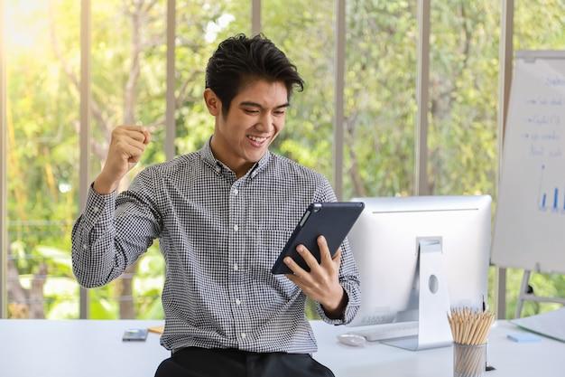 タブレットを保持し、コンピューターと会議ボードと机の上の付属品の作業室で喜んで上げられた拳を感じてスマートな若いアジア系のビジネスマンの肖像画。