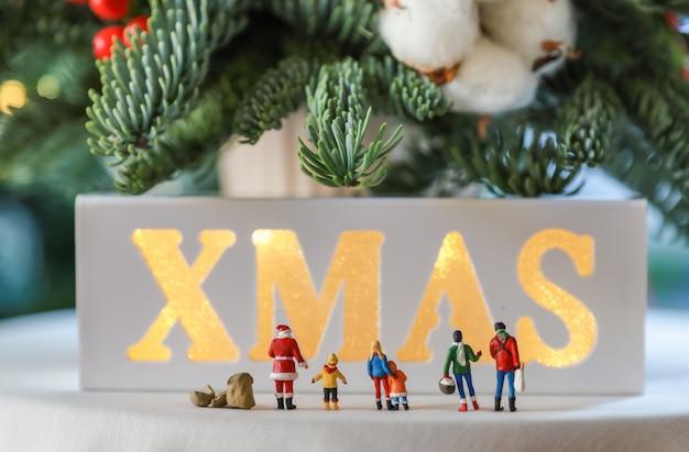 クリスマスとホリデーシーズンのコンセプト。ミニチュアフィギュア人男性女性子供の近く