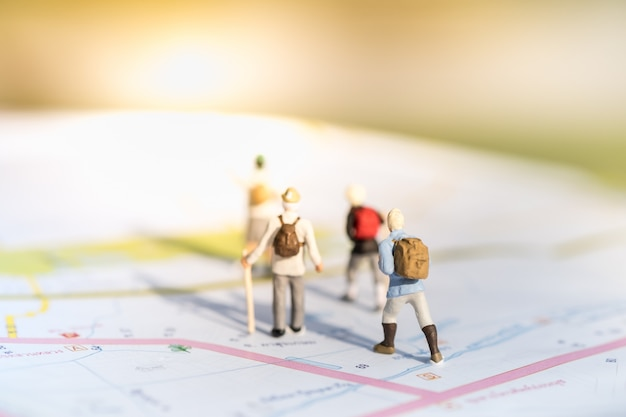 ミニチュアミニフィギュアのグループスタンドと地図の上を歩く