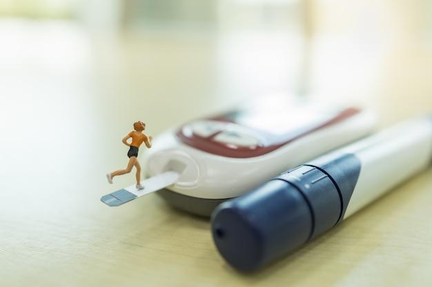 医学、糖尿病、血糖、医療、人々の概念-血糖テストストリップで実行されている女性ランナーミニチュア図のクローズアップと木製のテーブルのグルコースメーターに接続します。