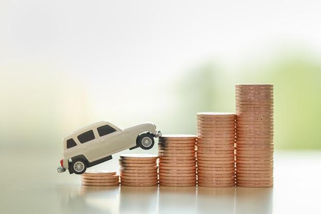 Концепция финансирования автомобильного бизнеса. закройте вверх белой миниатюрной игрушки автомобиля на стоге монеток с космосом экземпляра.