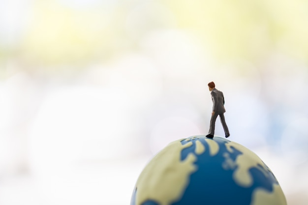 グローバルビジネスと計画のコンセプト。コピースペースを持つ世界のミニボールの上を歩くビジネスマンのミニチュアフィギュアの人々のクローズアップ。