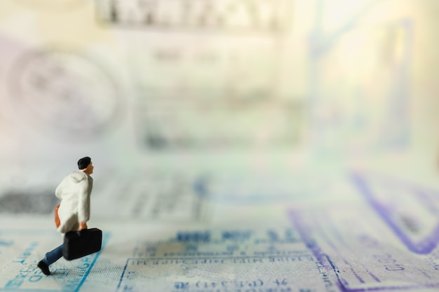 出張や旅行のコンセプトです。ハンドバッグとスーツケースに移民スタンプとコピースペースのパスワードを実行しているビジネスマンのミニチュアフィギュアの人々のクローズアップ。