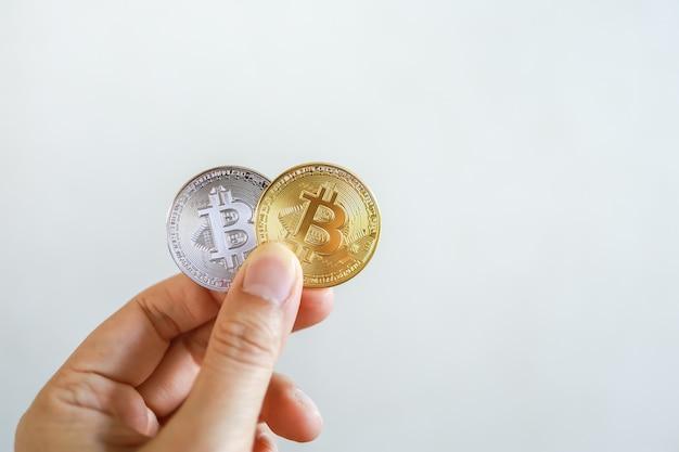 お金、金融、暗号通貨の概念。コピースペースを持つ男の手に金と銀のビットコインコインのクローズアップ。