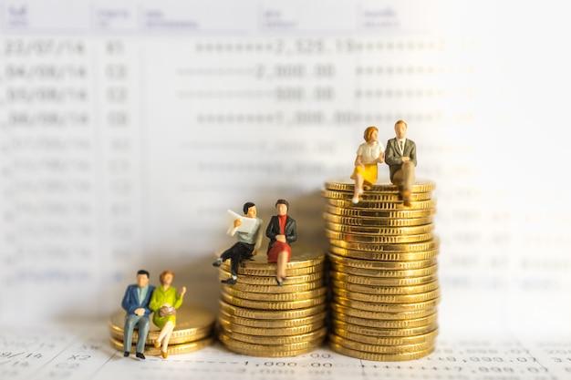 ビジネス、お金、金融、安全、節約のコンセプト。ビジネスマンと女性のミニチュアフィギュアの人々のグループが座っていると銀行通帳の金貨のスタックで会議を話している。