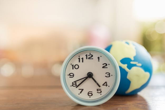 木製のテーブルにミニの世界のボールとヴィンテージの丸い時計