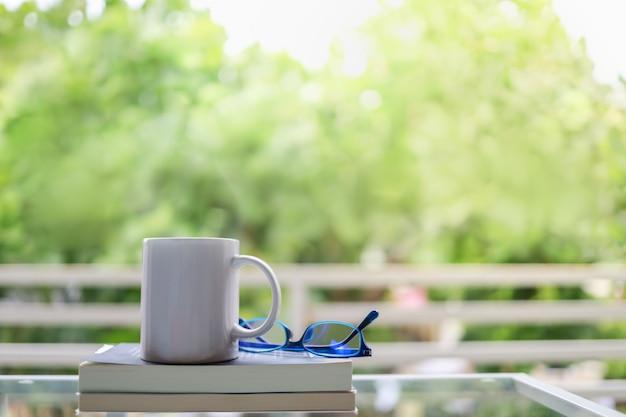 趣味、リラクゼーション、レクリエーションのコンセプト。老眼鏡とコピースペースのある庭で本とホットコーヒーの白いマグカップのクローズアップ。