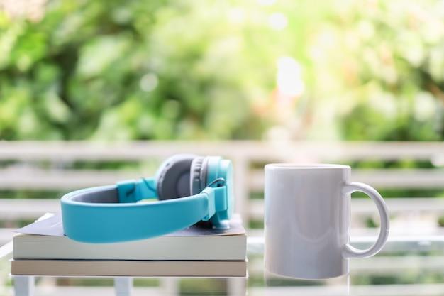 ヘッドフォンでホットコーヒーとコピースペースのある庭で本の白いマグカップのクローズアップ。
