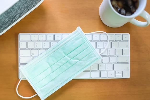 マグカップのアイスコーヒーと木製のテーブルのスピーカーと白いコンピューターのキーボード上の外科用フェイスマスクの平面図です。