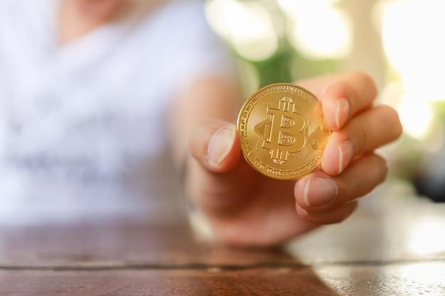 木製のテーブルに金のビットコインコインを持っている人間の手のクローズアップ。