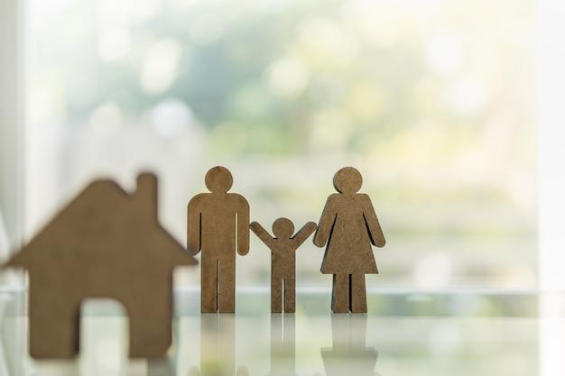 Деревянный мужчина женщина и ребенок значок с значок дома на столе с копией пространства.