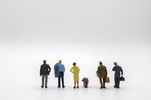 ジャケットとスーツケースとハンドバッグの白い背景の上に立っているビジネスマンとビジネスウーマンのミニチュアフィギュアの人々のグループ。