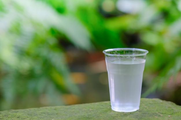 庭の石の上に冷たい水のプラスチック製のコップのクローズアップ。