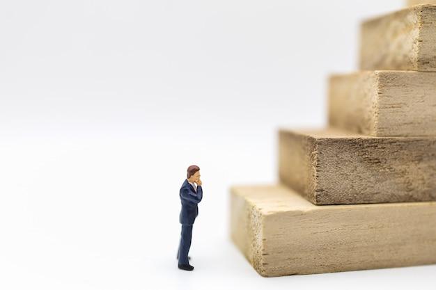 白い背景の上の木製のブロックのスタックを探しているビジネスマンのミニチュアフィギュアの人々のクローズアップ。