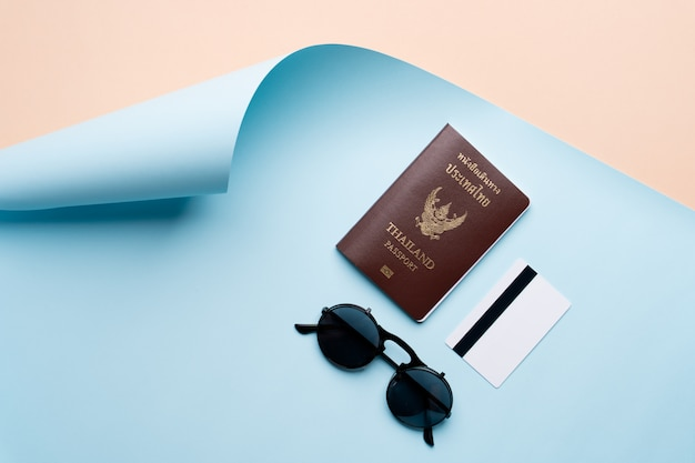 パスポート、クレジットカード、サングラスと抽象的なビーチの背景上の平面図旅行の概念
