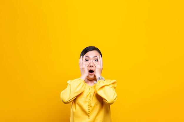 Женщина чувствует себя напуганной стоя над желтой стеной