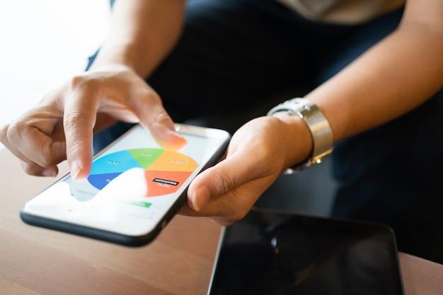 Азиатская женщина, глядя на некоторые графики на своем мобильном телефоне, сидя в кафе