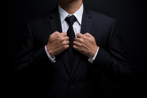 Мужчина в черном костюме поправляет галстук