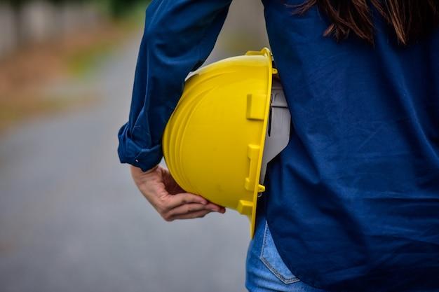 Женский инженер, держащий защитный шлем