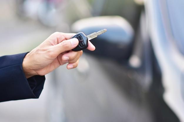 Продавец держит ключ от машины и машина припаркована