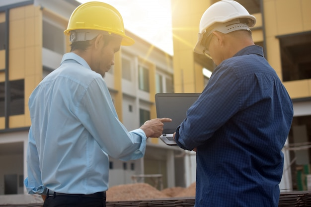 Инженеры с помощью компьютера на строительной площадке