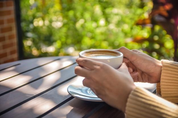木製テーブルの上のコーヒーカップを保持している人