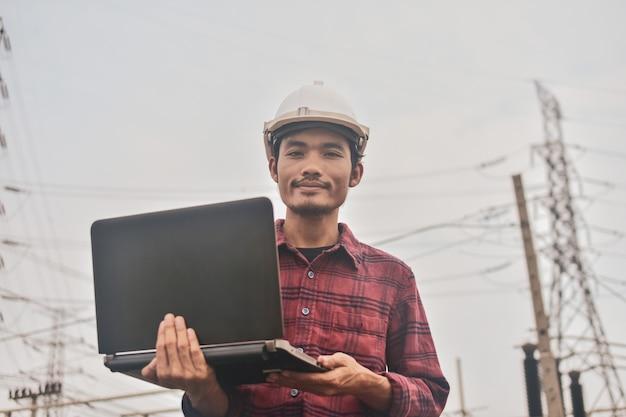 Бизнесмен держит компьютер на строительной площадке