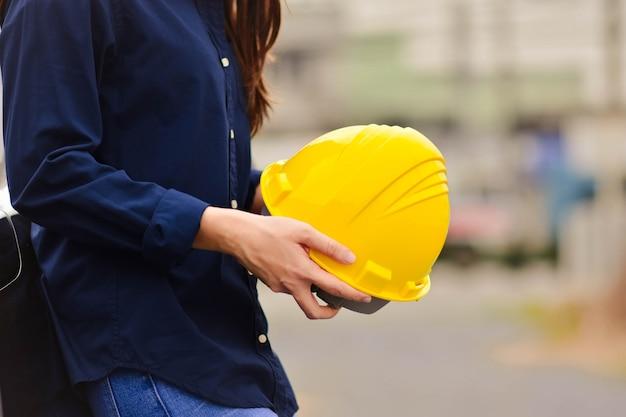 Инженер держит желтый шлем каску