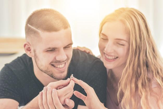 結婚指輪をクローズアップバレンタインの日の愛の概念で寝室の幸せに住んでいるカップルとリングと結婚することを提案するカップル
