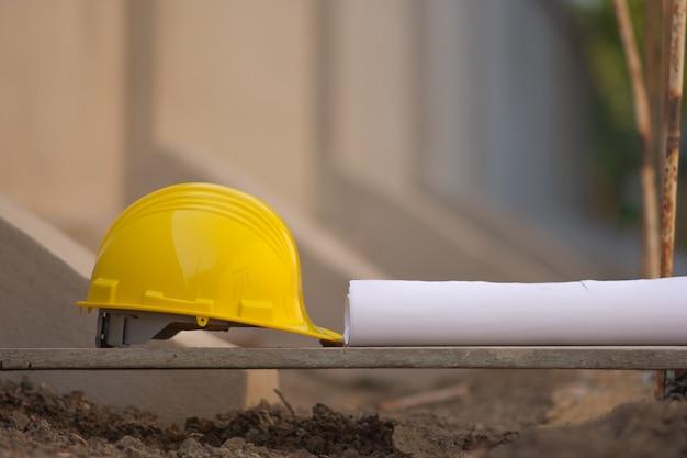 Каска на деревянной доске и план строительства здания недвижимости проект развития