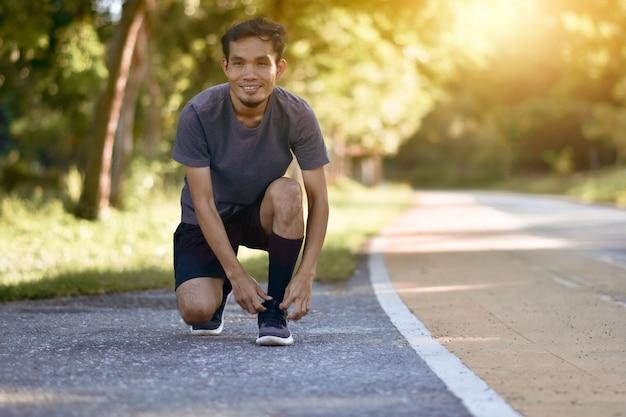 都市公園の朝屋外で走っているアジアランナー男
