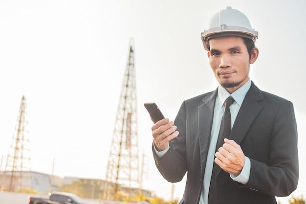ビジネスマンは、建設現場で携帯電話やモバイルのスマートフォンを呼び出す