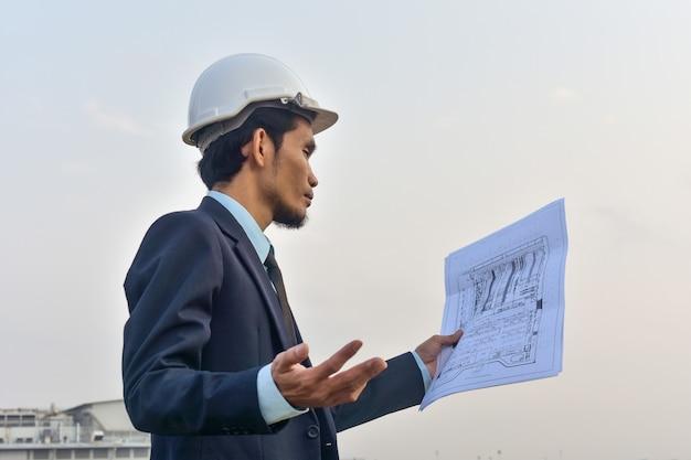 Бизнесмен, холдинг план стоял на открытом воздухе на строительной площадке