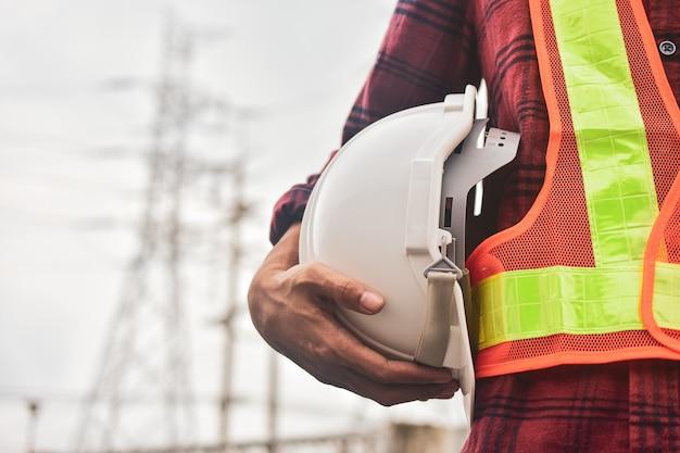 Инженер держит белый шлем безопасности каску копировать спецификацию