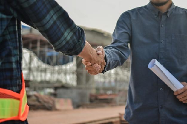 Руководитель пожимает руку форману успешное соглашение по проекту строительства здания