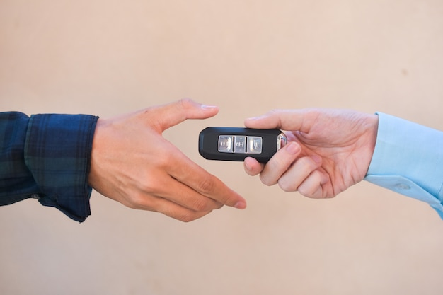 Закройте вверх по руке держа концепцию автомобиля ключевой продажи, дайте и возьмите ключевой автомобиль