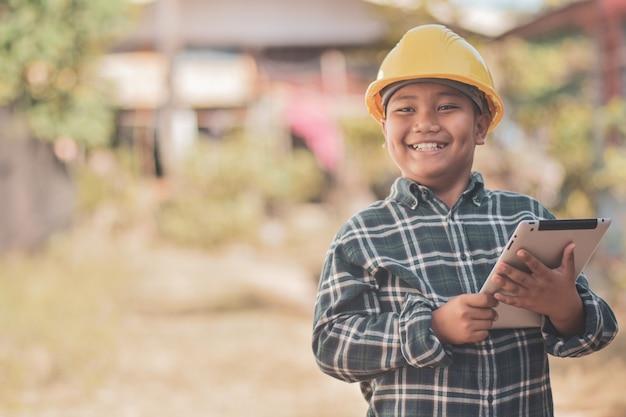 Мальчик ребенок желтый шлем каска безопасность инженерные концепции, держа планшет