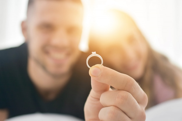 結婚指輪をクローズアップバレンタインの日の愛の概念で寝室の幸せに住んでいるカップルとリングとの結婚を提案します。