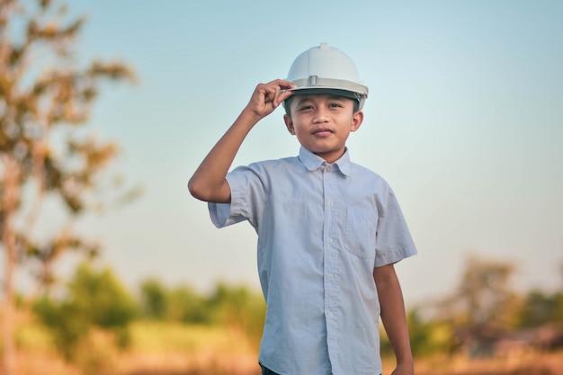 Мальчик малыш инженер держит шлем мечта инженерной концепции будущего