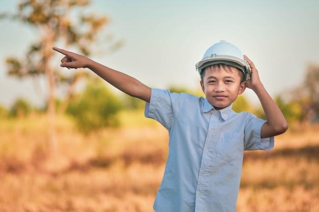 Инженер ребенк мальчика стоя внешняя держа концепция успеха руки