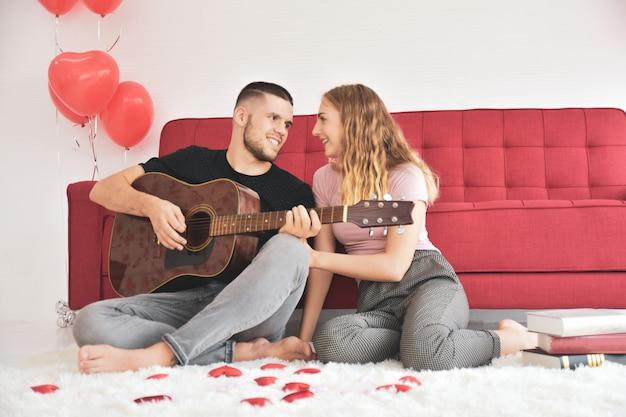 愛のバレンタインの日にロマンチックな幸福の部屋でギターを弾く少年少女