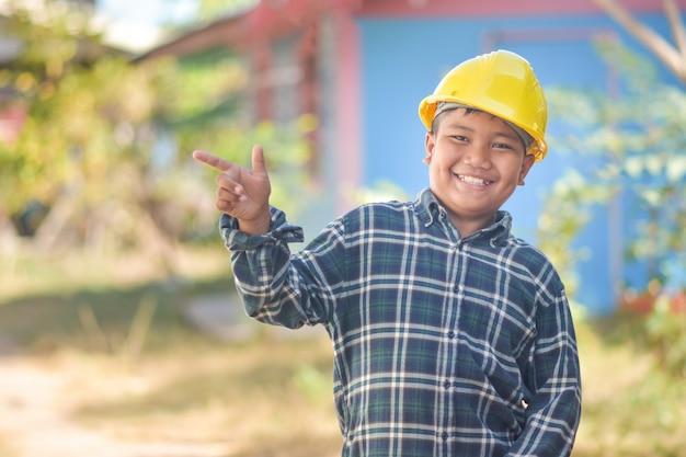 Мальчик инженер строительство заполнить счастливой улыбкой весело в действии инженерный желтый шлем