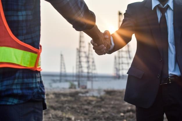 Инженер двух человек пожимает руку договору на проект усадебного строительства