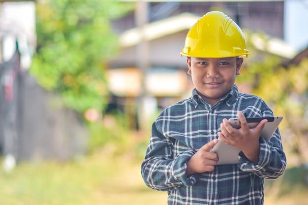 Мальчик малыш держать планшет использовать каску инженер строительство